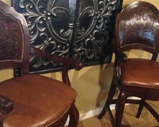 Two of four matching handsome leather & tooled bar stools/bistro table chairs; another fleur-de-lis metal wall art