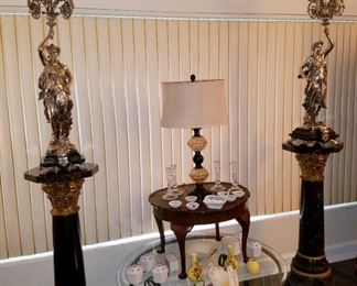 Matched pair of bronze sculptures/candelabras with quadruple sterling silver plate. Sculptor was Jean Louis Gregoire (1840-1890) from France.  They adorn heavy marble bases. In the center, there are 2 accent tables, several vases, crystal candlesticks, & Lenox swans.