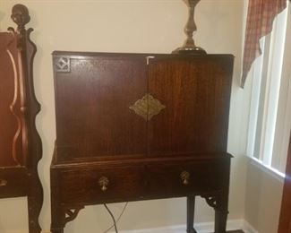 Antique buffet with silver drawer. Brass table lamp.