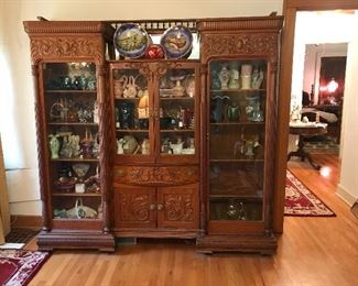 This amazing curio/china cabinet made entirely of oak with wonderful carving, fret work, mirror and beautiful detail.  Appears to be 3 pieces when in fact it is 1 piece.  Full of Fenton!