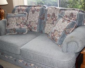 Blue fabric love seat.