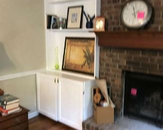 In the living room area are pictures, more clocks, another four drawer chest and more books