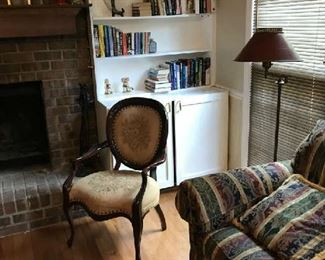 A view of antique casual chair; antique lamp, and some of the books for sale; plus a mantel clock