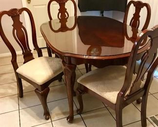 Dining room table with glass cover and upholstery chairs.