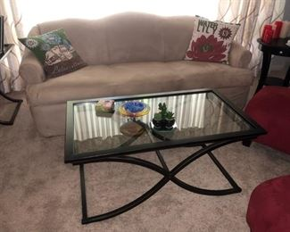 Neutral upholstered couch and glass/metal coffee table