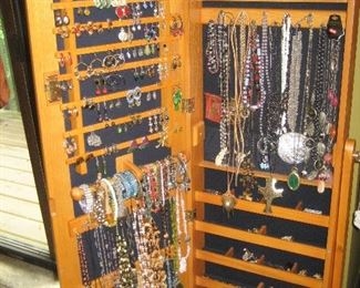 Wooden jewelry cabinet with assorted jewelry