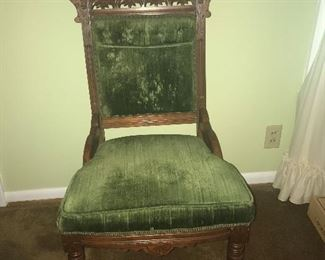 Antique upholstered carved back side chair on rollers