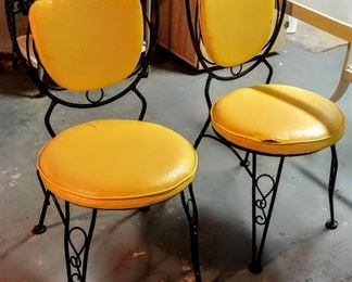 retro rod-iron bistro chairs with yellow cushions