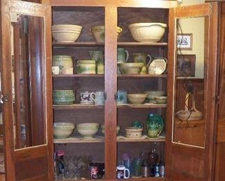 Oak cabinet Yellowware bowls, pitchers, butter crocks