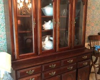 China cabinet full of china and evidently a burning candelabra on the upper left there