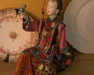 Asian porcelain figure consorting with bird