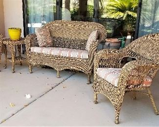Wicker outdoor settee and two chairs and side table. Large black trunk great for storing outdoor items or by the pool for pool items.