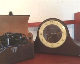 "One of a pair of 7x35 field glasses in leather cases by Empire; German mantle clock by ""Tradition"" (works) with keys"