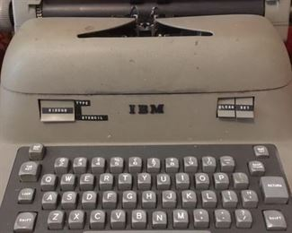 Electric typewriter by IBM with vinyl dust cover. Works but needs new ribbon.