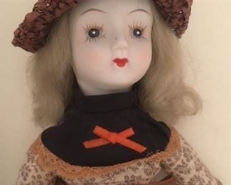 Antique bisque doll dressed in calico with painted eyes and shoes, cloth body