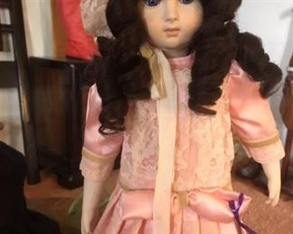 Hand-made brunette porcelain doll with cloth body dressed in pink by native Louisianan and Texas/Colorado potter/artist Ann Fontonat