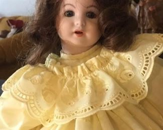 Antique brunette bisque doll dressed in yellow  with glass eyes and open mouth, back of neck stamped 247 PARIS