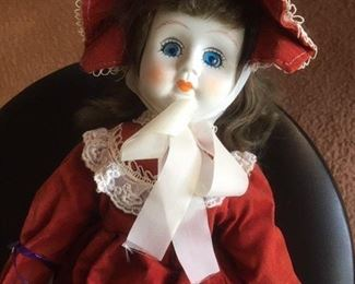 Antique bisque brunette doll dressed in red with glass eyes, painted lashes, cloth body and black leather boots