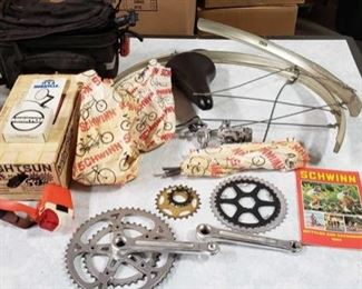52: 	 Schwinn bike parts, catalog, bike gear, travel bag Miscellaneous bicycle parts for Schwinn model including a 1980 Schwinn bicycle catalog, ESGE wheel covers, sprockets, braking gear, padded handlebar seat, Nightsun dual beam team issue bike-mounted night light, and a Jandd mountaineering bike bag.