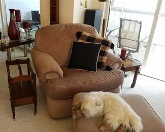 Overstuffed chair & ottoman with cat-form stuffed animal looking right at home!