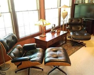 View in Den featuring a matching pair of Eames Lounge chairs (670) with ottomans (671).  Wood and leather in good condition.  Chairs estimated to be about 20 years old, per family.