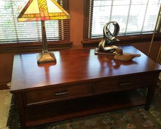 Low table (top is cantilevered to come up and over the lap of someone seated in front of it),  leaded glass lamp, etc, in the Den