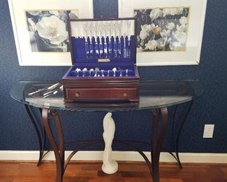 Glass top iron base demilune table displaying set of silverplate flatware.  Spring flower artworks on wall.