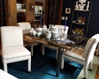 Metal frame dining table.  Ends pull out to accommodate the self-storing leaf.  Set of 6 white upholstered chairs.