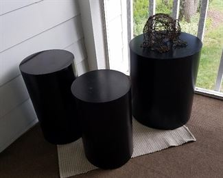 Black display cylinders, one with wire frog sculpture