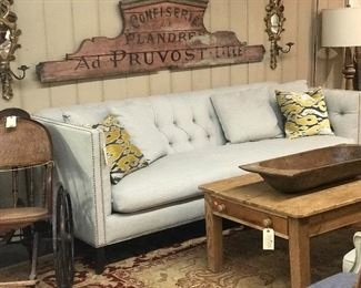 Modern tufted sofa in gray. Trimmed with silver nail heads.