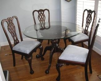 Round table with glass top and 4 Chippendale style chairs