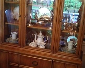 Cherry china cabinet filled with silver plate and ceramic dishes