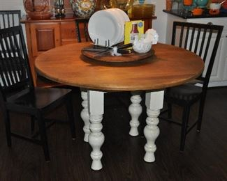 """48"""" round wooden Kitchen Table from Hudson Dry Goods, NYC with ivory Shabby Chic wooden legs  shown with a set of 4 black painted wood dining chairs from Crate and Barrel"""