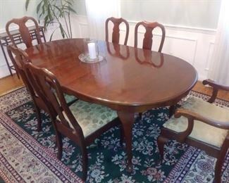 Cherry dining room table with six matching chairs and two leaves