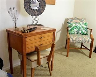 Vintage sewing machine cabinet with original sewing machine. Also the original chair that opens up to hold sewing notions.