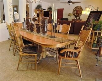 Large oak dining table with 8 chairs. It also has leaves that can come out to make the table smaller.