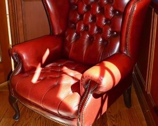 One of a pair of red leather wing back chairs
