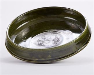 Warren MacKenzie (1924-2018). Large low studio ceramic pottery bowl with an inverted rim. Stoneware with mossy green glaze. Warren MacKenzie was a renowned Minnesota studio potter. A student of Bernard Leach and Shoji Hamada, he is credited with bringing the functional Mingei tradition to the United States, and spreading it through his own art and mentorship of students during his long tenure at the University of Minnesota. Note: Lots 1-19 were purchased by a single collector from MacKenzie's showroom between 1989-2000 SKU: 01390 Follow us on Instagram: @revereauctions