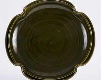 Warren MacKenzie (1924-2018). Large studio pottery ceramic platter with a lobed shape and split rim. Stoneware, glazed in an elegant, earthy dark green. Warren MacKenzie was a renowned Minnesota studio potter. A student of Bernard Leach and Shoji Hamada, he is credited with bringing the functional Mingei tradition to the United States, and spreading it through his own art and mentorship of students during his long tenure at the University of Minnesota. Note: Lots 1-19 were purchased by a single collector from MacKenzie's showroom between 1989-2000 SKU: 01397 Follow us on Instagram: @revereauctions