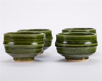 Warren MacKenzie (1924-2018). Set of four studio pottery ceramic bowls. Stoneware with dark green glaze. Marked along the footrim. Warren MacKenzie was a renowned Minnesota studio potter. A student of Bernard Leach and Shoji Hamada, he is credited with bringing the functional Mingei tradition to the United States, and spreading it through his own art and mentorship of students during his long tenure at the University of Minnesota. Note: Lots 1-19 were purchased by a single collector from MacKenzie's showroom between 1989-2000 SKU: 01403 Follow us on Instagram: @revereauctions