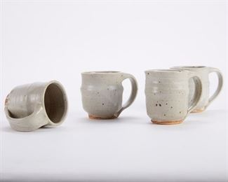 Warren MacKenzie (1924-2018). Set of four studio pottery ceramic mugs. Stoneware with white glaze and gray interiors. Marked along the footrim. Warren MacKenzie was a renowned Minnesota studio potter. A student of Bernard Leach and Shoji Hamada, he is credited with bringing the functional Mingei tradition to the United States, and spreading it through his own art and mentorship of students during his long tenure at the University of Minnesota. Note: Lots 1-19 were purchased by a single collector from MacKenzie's showroom between 1989-2000 SKU: 01404 Follow us on Instagram: @revereauctions