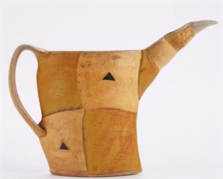 Jeff Oestreich (b. 1947). Beaked pitcher. Soda-fired stoneware. Signed below the handle. Jeff Oestreich was first introduced to ceramics as a student of Warren MacKenzie's at the University of Minnesota. Inspired, he went on to apprentice with Bernard Leach in St. Ives, then settled back in Minnesota to form his own pottery. He is an active part of the Minnesota ceramics community, hosting a stop on the St. Croix Valley Pottery Tour, and he is also active on a larger scale: he is displayed in many museums throughout the world and has taught and done artist residencies in a varied group of institutions, including the Rhode Island School of Design, Leach Pottery in St. Ives, and Haystack Mountain School of Crafts in Maine.  SKU: 01214 Follow us on Instagram: @revereauctions