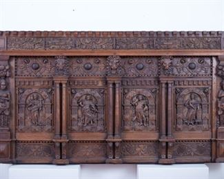 German wood mantel, profusely carved with religious motifs. Assembled c. 19th century of older components. Four panels depict saints, surrounded by arches and columns with historiated capitals with lion heads and plinths. The mantel is flanked by herms and framed by scrolling foliate and grape designs on the top and bottom registers.  SKU: 01853 Follow us on Instagram: @revereauctions