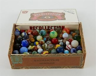 A large group of vintage glass marbles of varying sizes. With vintage cigar box.  SKU: 01874 Follow us on Instagram: @revereauctions