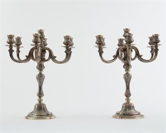 Pair of 800 silver Italian candelabra, c. 20th century. Each with a central nozzle and drip pan, baluster stem with six branches extending from it, each terminating in a nozzle and drip pan. Profusely decorated with scrolling floral designs. Marked 800 and with an illegible maker's mark along the top of the base.  SKU: 01843 Follow us on Instagram: @revereauctions