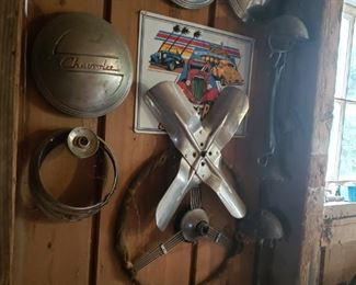 Vintage hubcaps and steering wheel and old licence plates