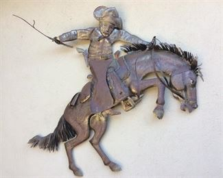 Commissioned brass horse and cowboy, very large piece, is hanging outside and has nice patina