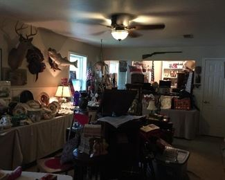Looking into the game room.  This room is very full, furniture, china, glass, taxidermy, musical instruments, books, and sports collectables.