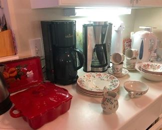 pretty red ceramic covered casserole dish, flowery dinnerware, coffee maker and back-up coffee maker