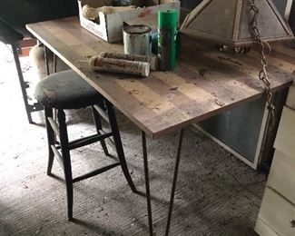 fab Metal butterfly table with hairpin legs. The leaves are underneath and when the table is pulled apart, the leaves pop up.   Old wooden stool with leather top and brass tacks.  Hanging light.  All items are being moved to the back porch